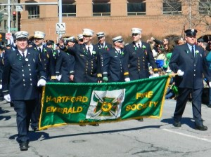 Back from military deployment in Afghanistan and back on the job as deputy chief of the Hartford Fire Department, Dan Nolan (center) marched with the Emerald Society.