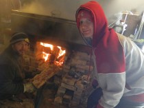 Dan and his son Tyler load seasoned wood from their property into the evaporator's burner.