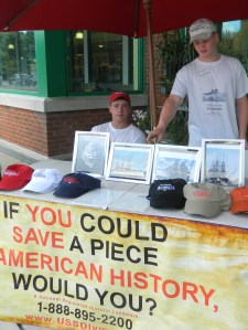 """Timothy Jarvis and Dalton Deakule man a """"SAVE the USS Olympia"""" table in Vernon, CT on July 27, 2013."""
