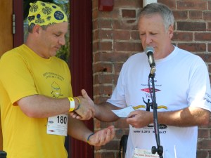 "Jason ""Jay"" Scott accepts a ceremonial check from Mike Deneen, part owber of Union Street Tavern during the 7th Annual Tavern Trot in Windsor, CT."