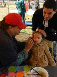 Fernando of Manchester holds his daughter Makayla's hair out of her face as Kevin Sterling paints on a pumpkin.