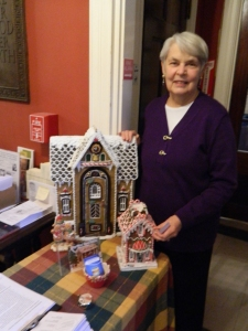 Volunteer Bobbi Cote with a gingerbread house she bought at Lux, Bond & Green.