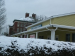Behind snowy bushes, the army Navy Club in downtown Manchester.