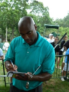 Photo by Jacqueline Bennett  Former UConn and NBA standout Scott Burrell signs autographs  during the Traveler's Championship Pro-Am Day in 2011.