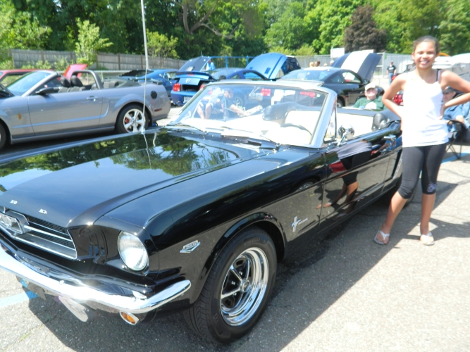 """Twelve-year-old Cassidy Jacobs is shown with her grandfather's """"1964 and a half"""" Ford Mustang June 1 at a Mustang Show in Manchester, CT. The model was introduced on April 17, 1964 at the New York's World Fair, the original """"pony"""" car."""