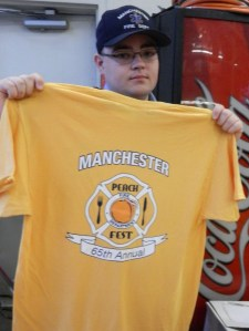 Dean Gates of the 8th Utilities Fire District shows t-shirts that were sold for the 65th Annual Peach Festival.