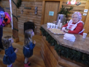 Juliana and Isla Mayer of Manchester enjoy apples from Mrs. Claus.