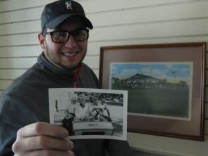 Patrick Kozelka holds a photo of his grandfather, Milton Kozelka, Sr. who served as club president circa the 1960s - he is shown at the wheel of the golf cart. In the background is a painting of the golf club.