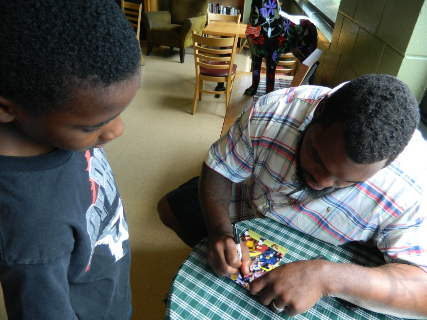 Chris Baker autographs a photo for Brendan Jenkins, 10, a student at Clover Street School in Windsor, CT where he plays football for the Windsor Giants.