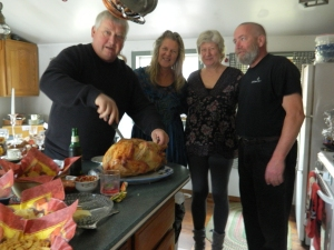 Mike carving the turkey. Beside him are Melane, her sister karen and Karen's husband Danny.
