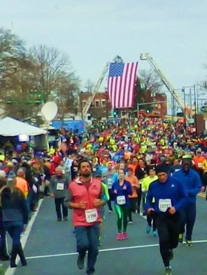 Runners pass under the American flag as they head for the 80th Manchester Road Race finish line.